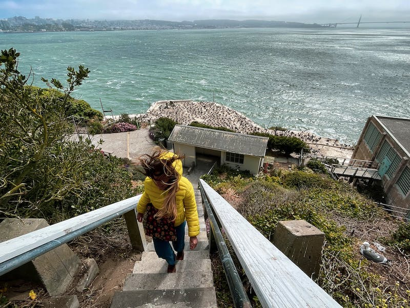 Woman walking up stairs overlooking the Pacific Ocean from Alcatraz Island