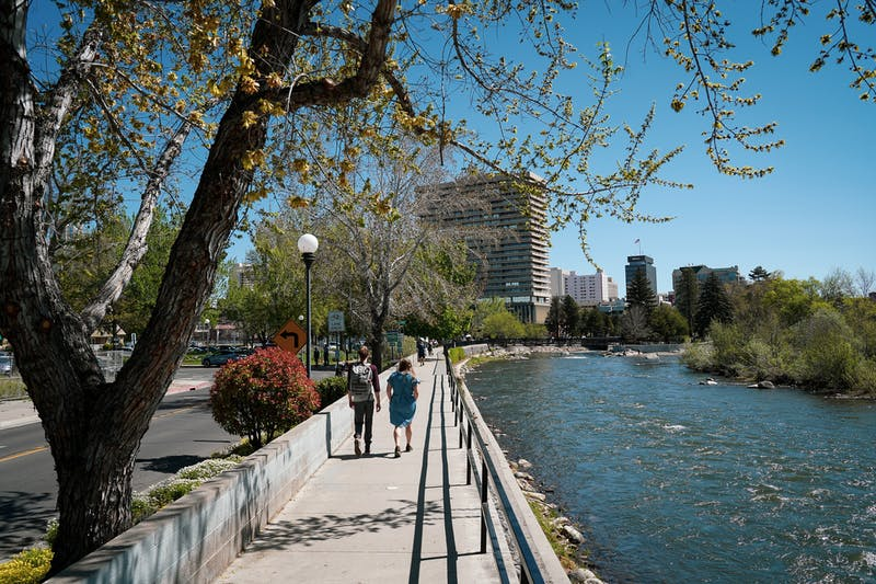 Couple walking the Reno Riverwalk along the Truckee River