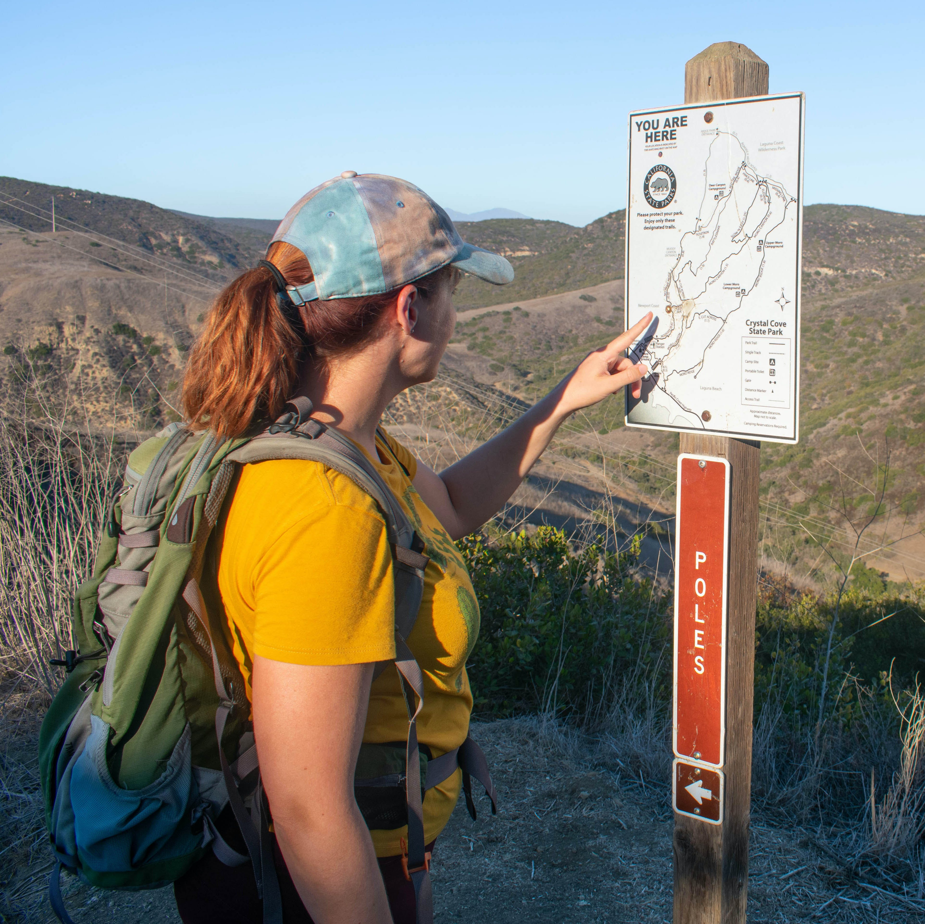 Hiker looking at map post at Crystal Cove State Park in Orange County