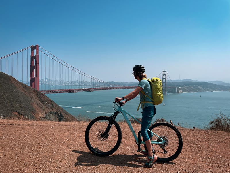 A biker stopped to take in the scenery on the fire road leading to Kirby Cove and overlooking the Golden Gate Bridge