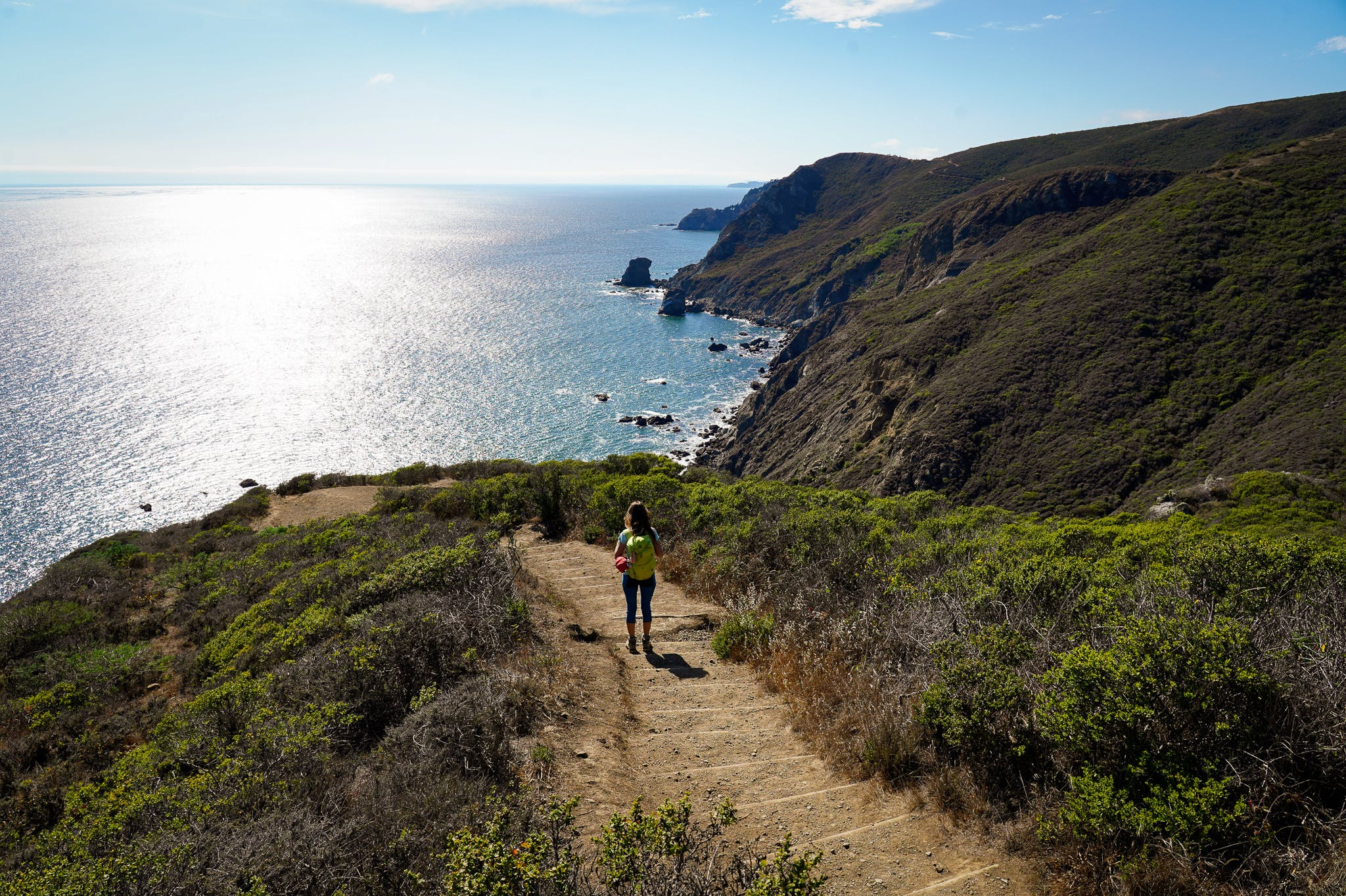 Woman descending dirt steps on the Coastal Trail in the Marin Headlands