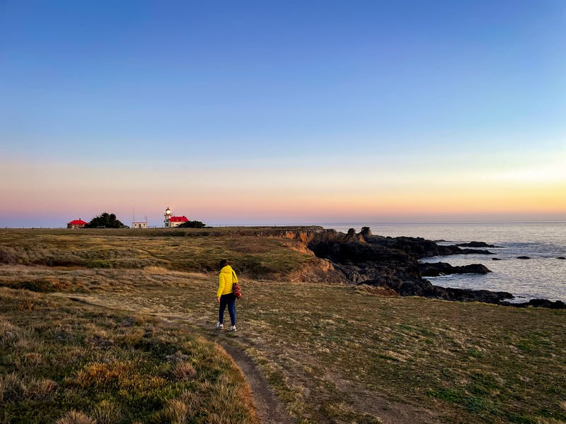 Woman hiking towards Point Cabrillo Light Station on the Mendocino Coast