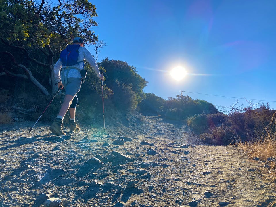 Hiker heading up a wide dirt trail at St. Joseph's Hill in Los Gatos