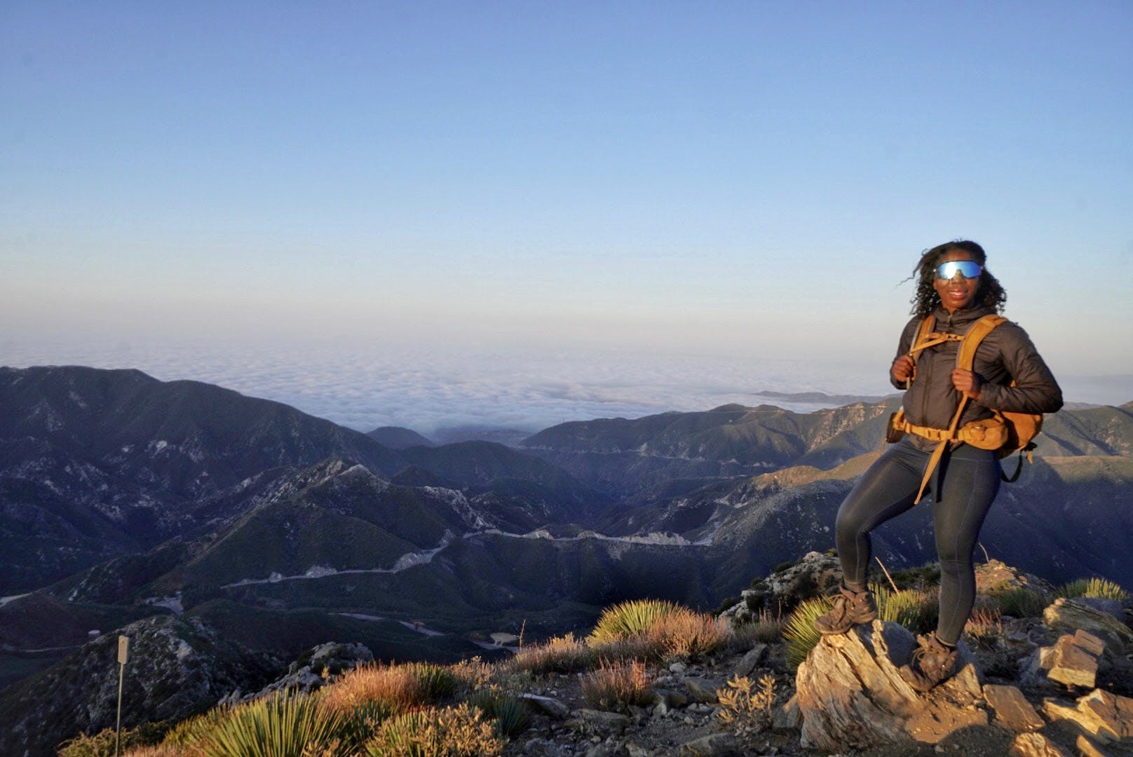 Woman standing at a viewpoint overlooking the San Gabriels at Josephine Peak
