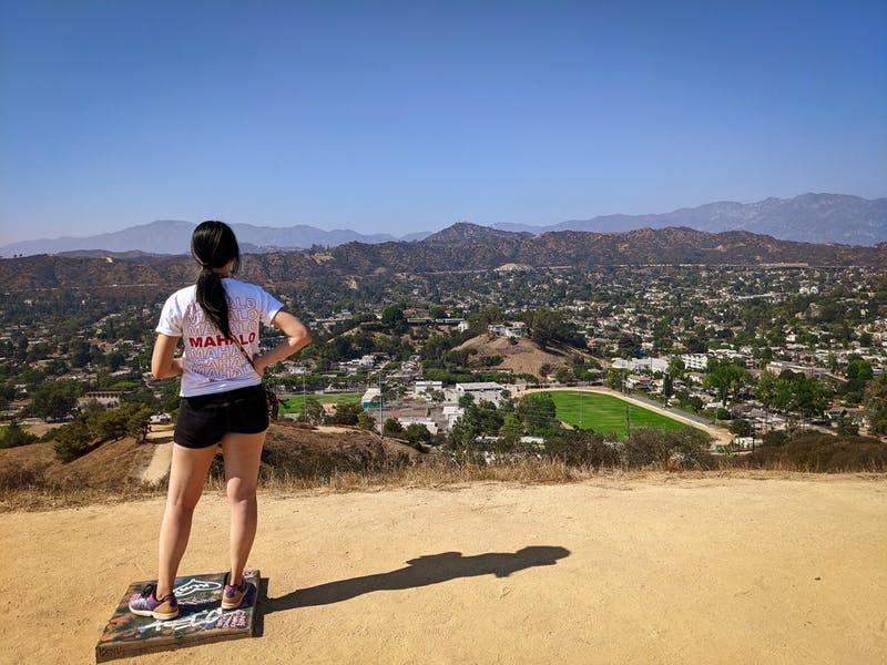 Hiker at the top of Fiji Hill overlooking the mountainous background in Los Angeles