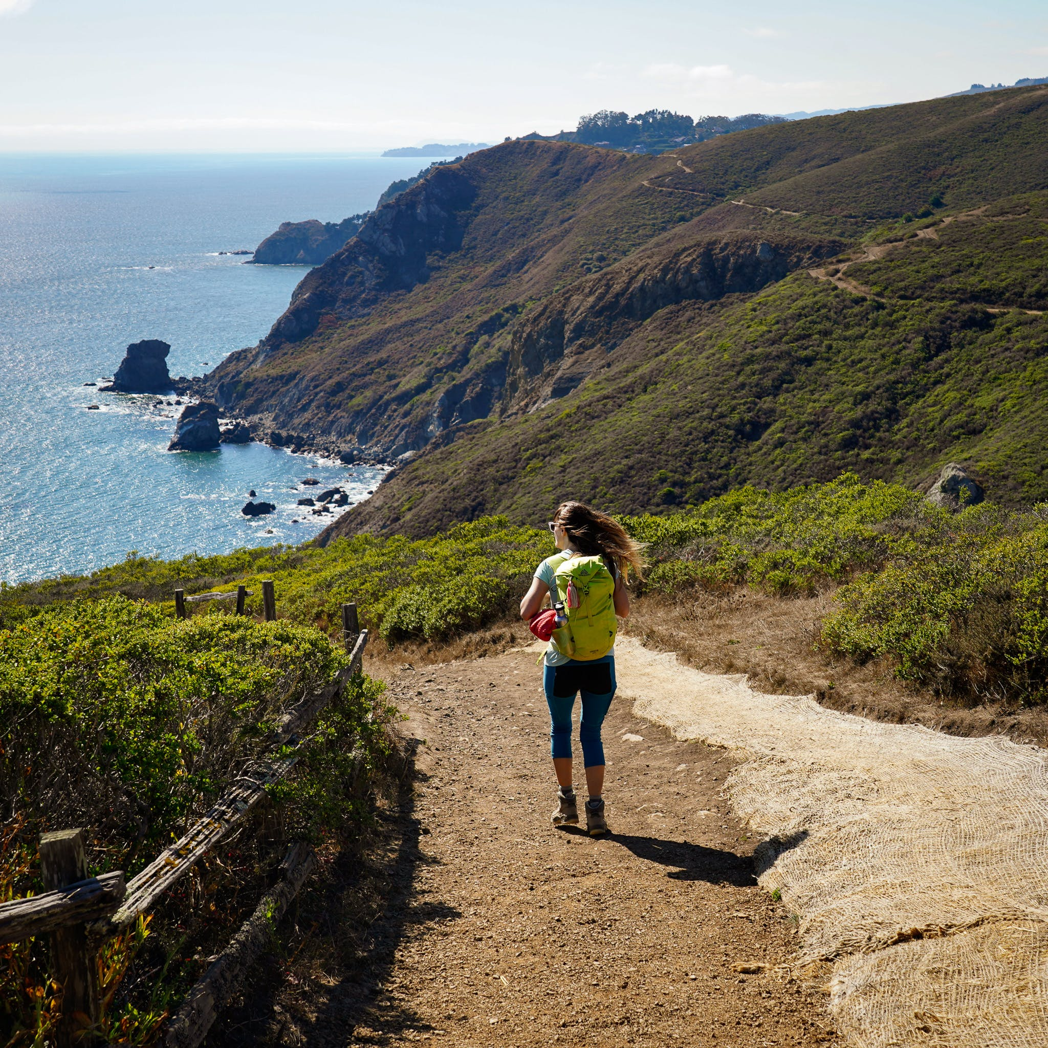 Woman hiking down the Coastal Trail in the Marin Headlands
