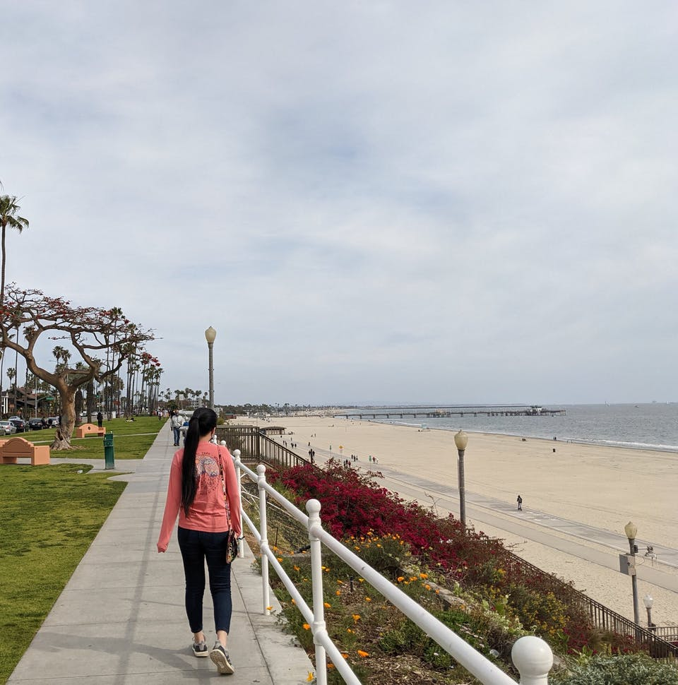 Woman walking along the sidewalk at Long Beach in Los Angeles County