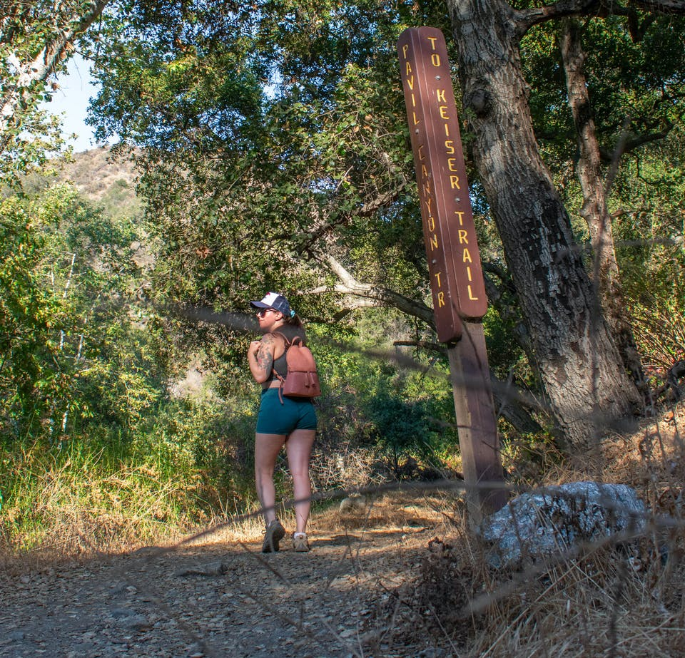 Woman hiking in a forest on the Keiser Trail in Big Dalton Canyon Wilderness Park in Los Angeles County