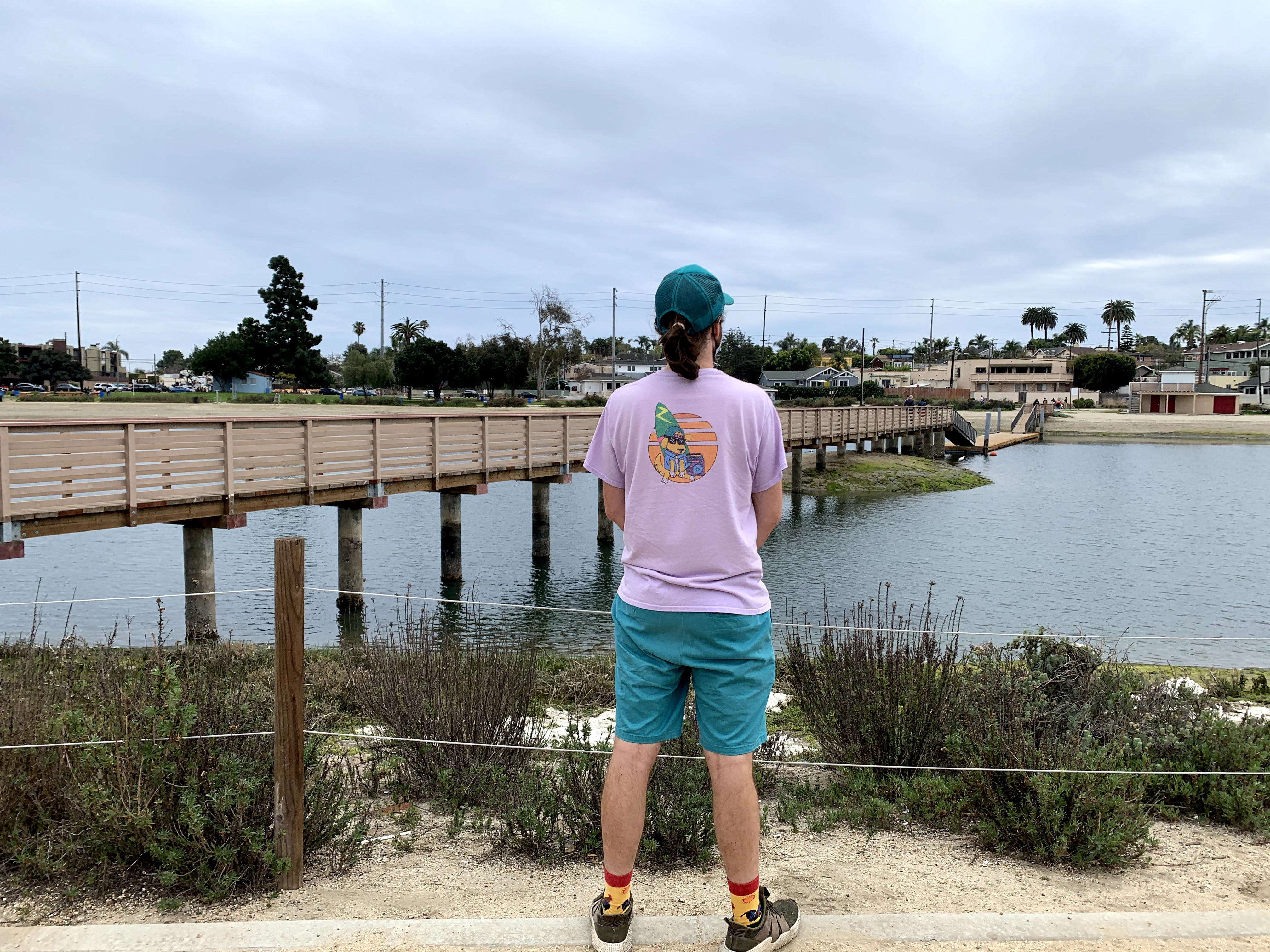 Man looking out towards a bridge at the Colorado Lagoon in Long Beach, Los Angeles County