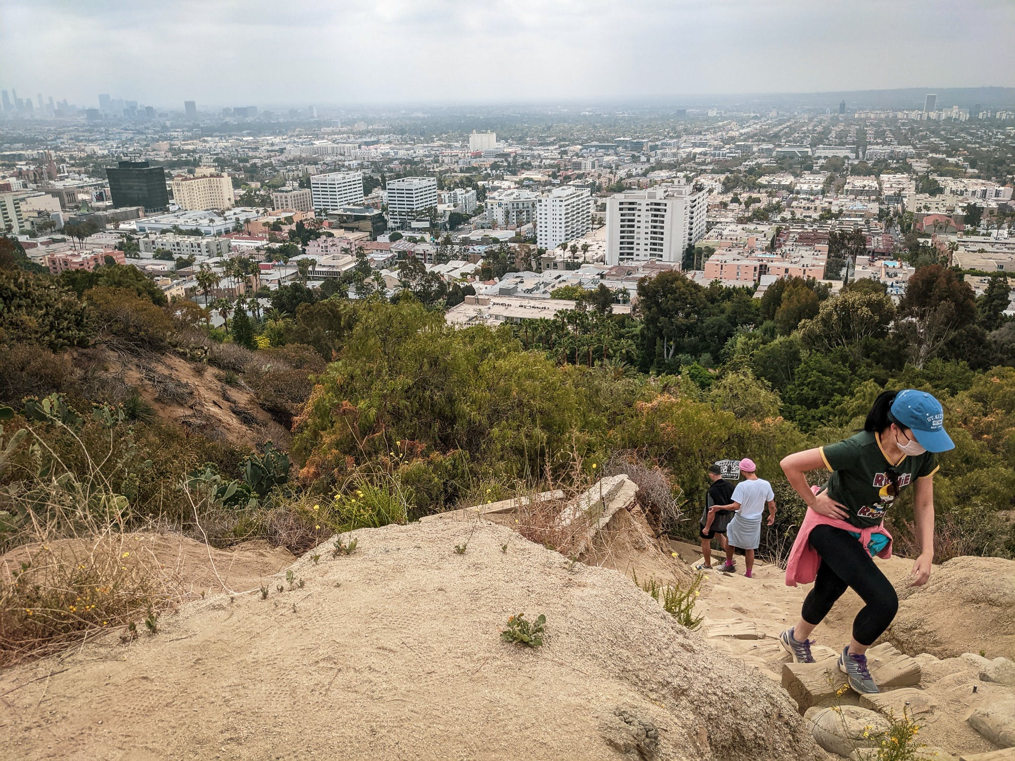 Hiker going uphill at Runyon Canyon with views of LA below in Los Angeles