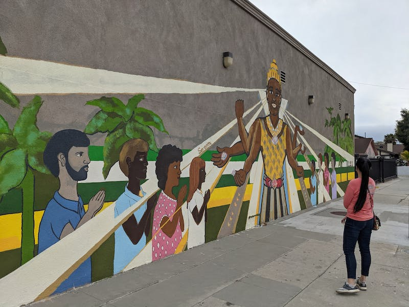 Woman standing an looking at mural wall art in Cambodia Town Long Beach Los Angeles