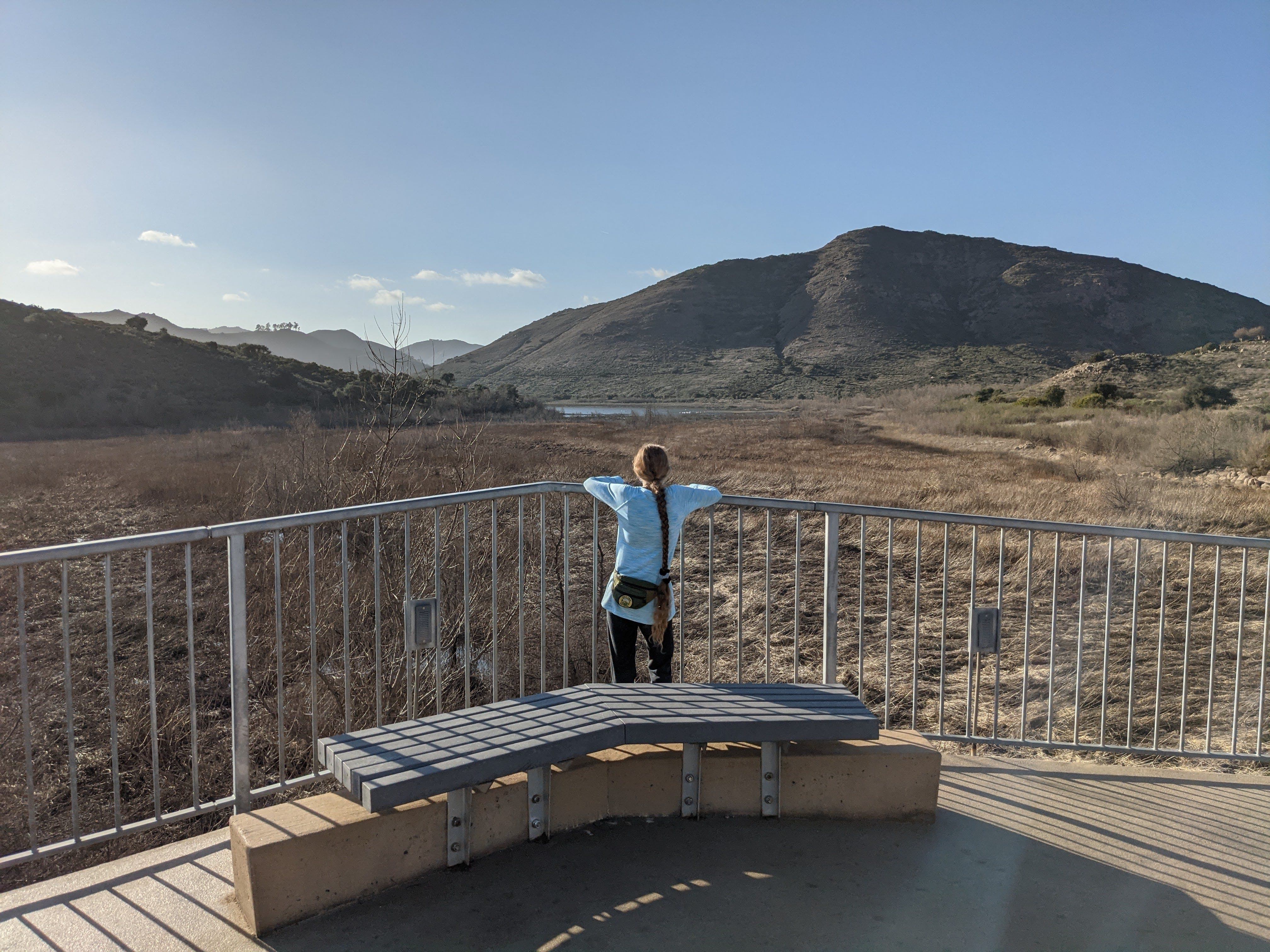 Woman standing at a bench area overlooking Lake Hodges at Lake Hodges Bicycle Pedestrian Bridge