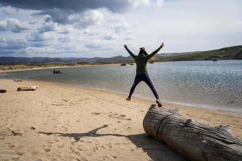 Woman jumping on the beach at Pescadero Marsh