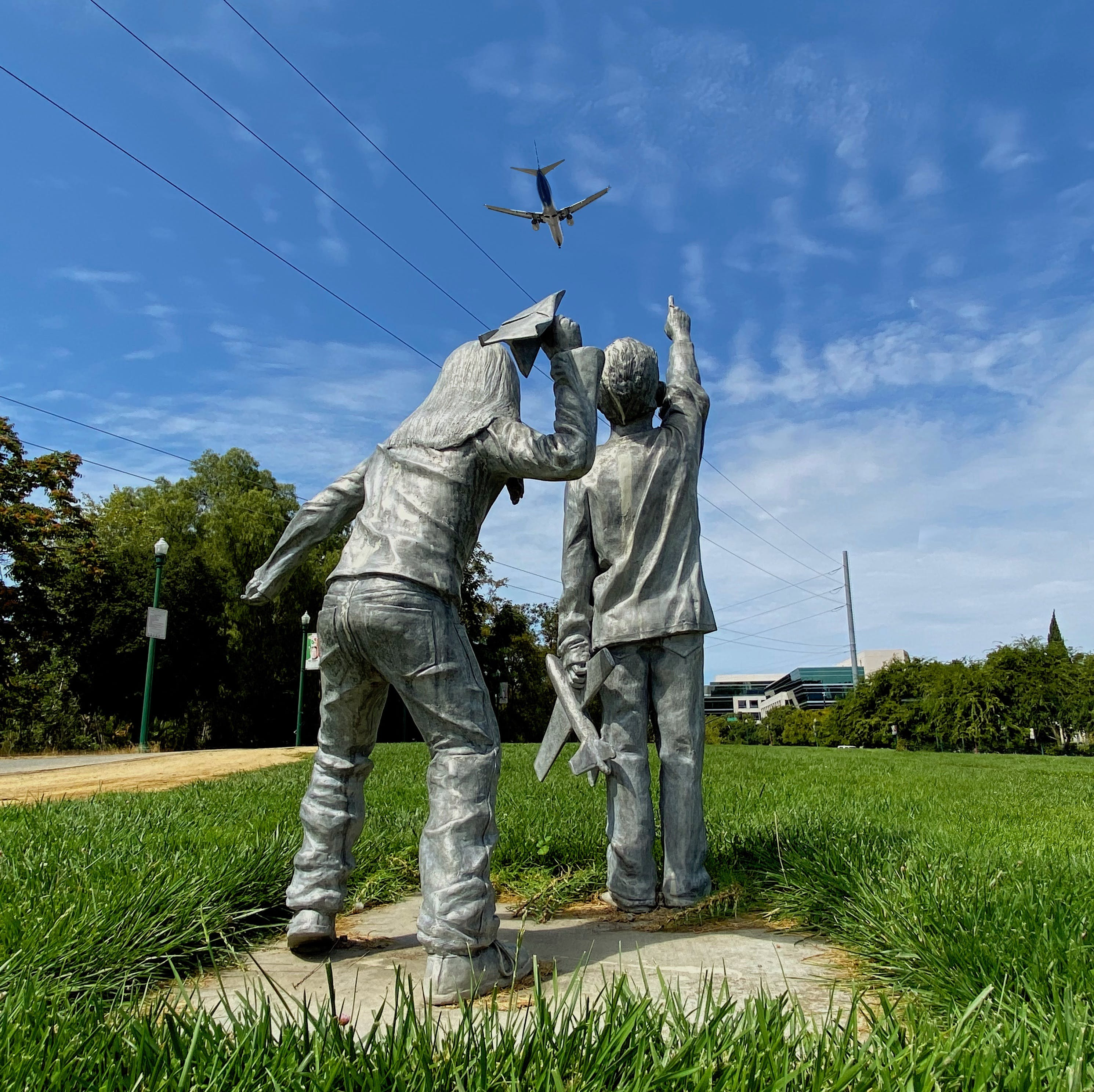 Sculpture of two kids pointing at the sky near the San Jose Airport with planes flying overhead