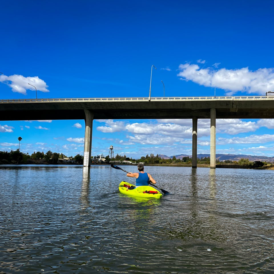 Kayaker paddling under a bridge on the Napa Valley River with Napa Valley Paddle
