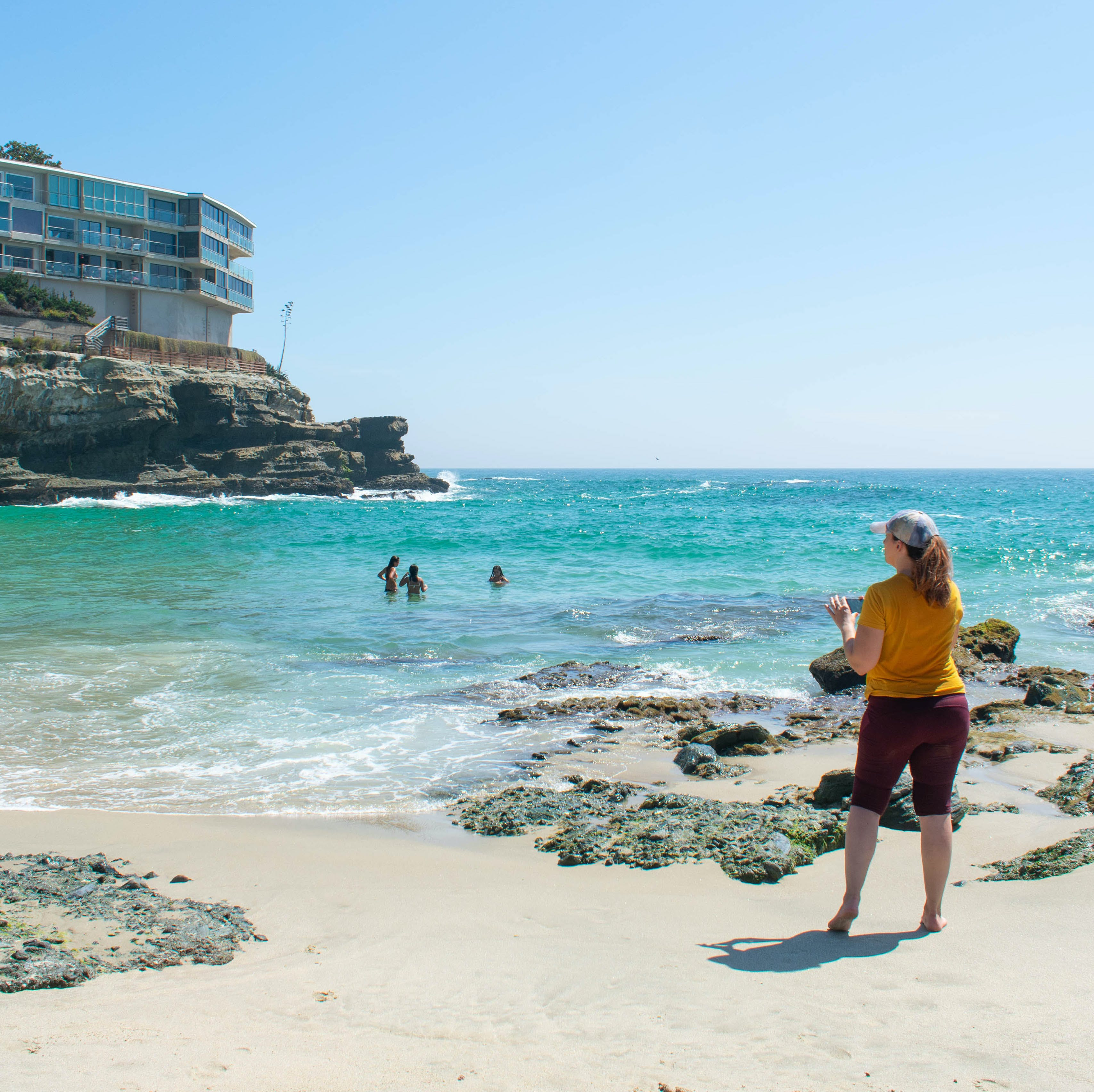 Woman standing at a turquoise beach cove at Coast Royale Beach in Orange County