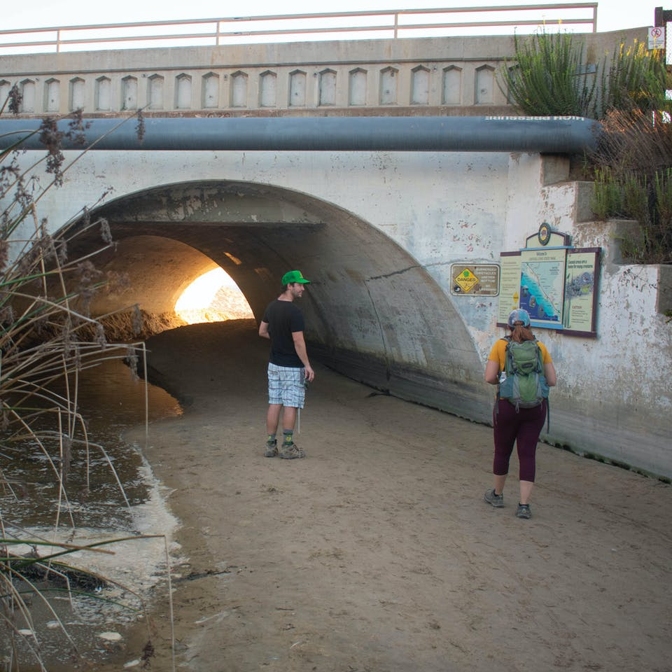 Two hikers passing through a tunnel leading to Crystal Cove State Beach in Orange County Southern California
