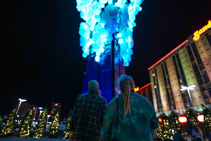 couple looking at neon art on neon line in Reno