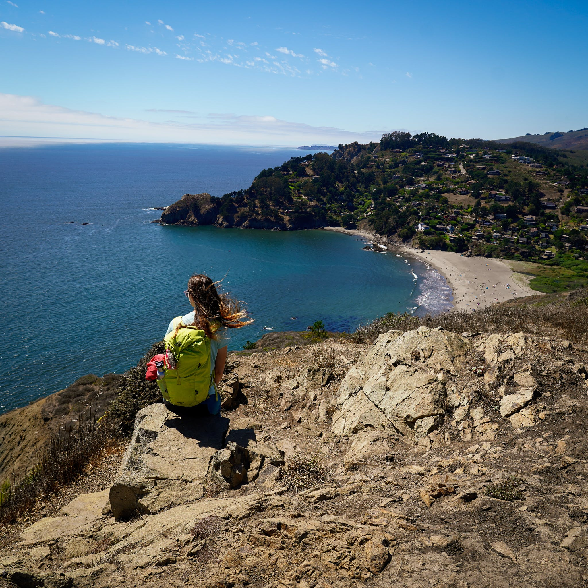 Woman sitting on a rock on the Coastal Trail and looking down below to Muir Beach in the Marin Headlands