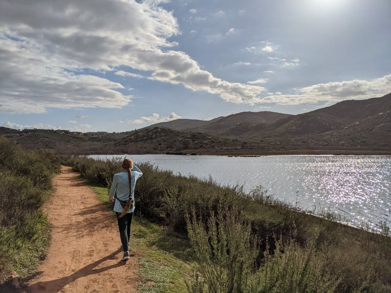 Woman walking the shoreline at Lake Hodges in Escondido San Diego County