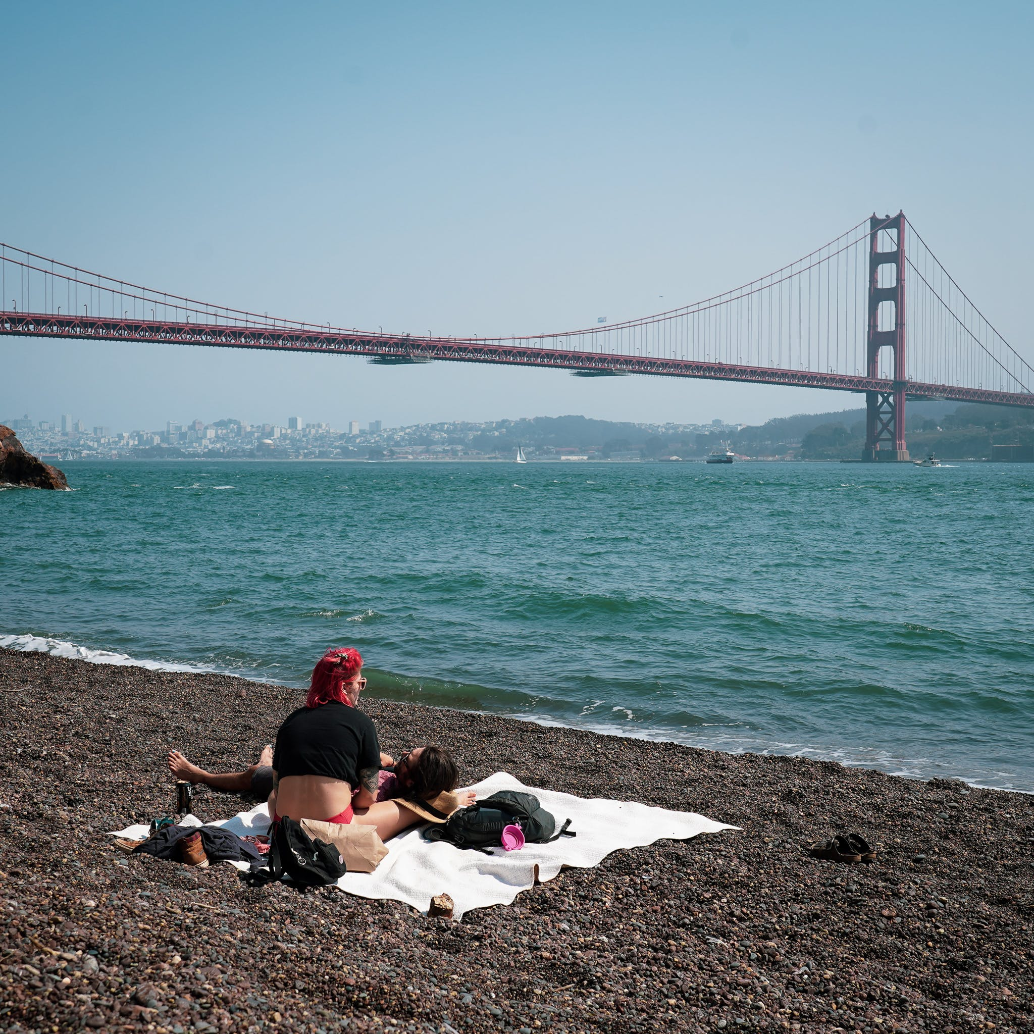 A few people relaxing on the beach at Kirby Cove with the Golden Gate Bridge in the background