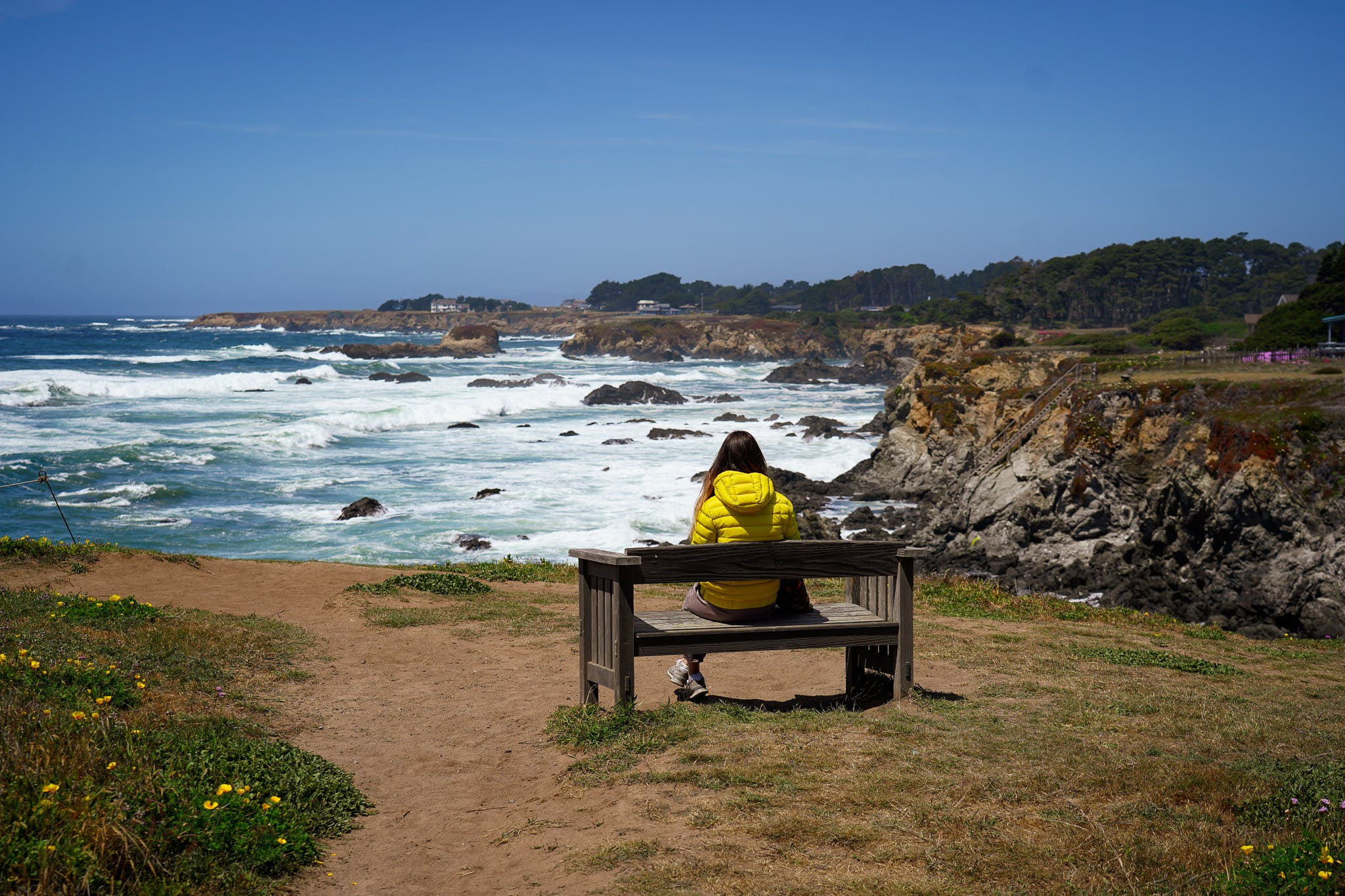 woman at a bench overlooking Mendocino coast
