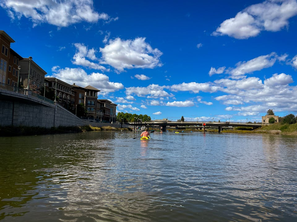 Paddler on the Napa River passing by downtown Napa and Stone Brewing