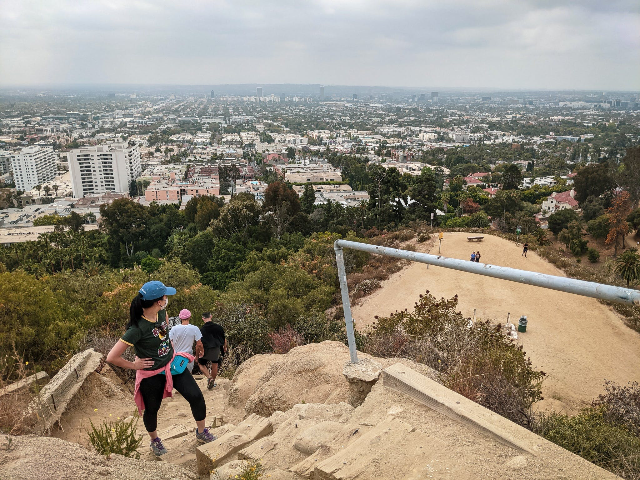Hiker taking a break on stair steps and looking out to the city view of LA at Runyon Canyon in Los Angeles