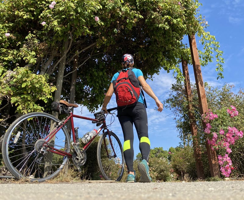 Woman with her bike at entering a garden along Guadalupe River Trail in San Jose