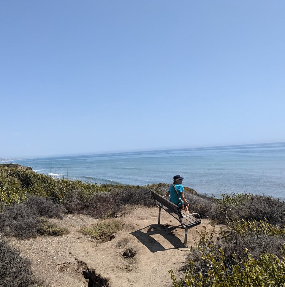 Woman sitting on a bluff top bench overlooking the Pacific ocean on the San Onofre Bluffs Loop Trail overlooking San Onofre State Beach in San Diego County