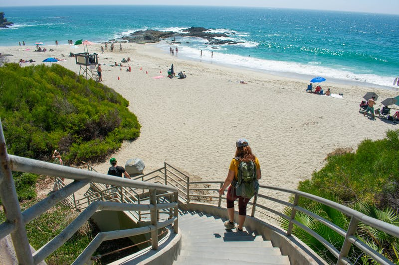 Woman hiking down the stairs to Coast Royale Beach in Orange County
