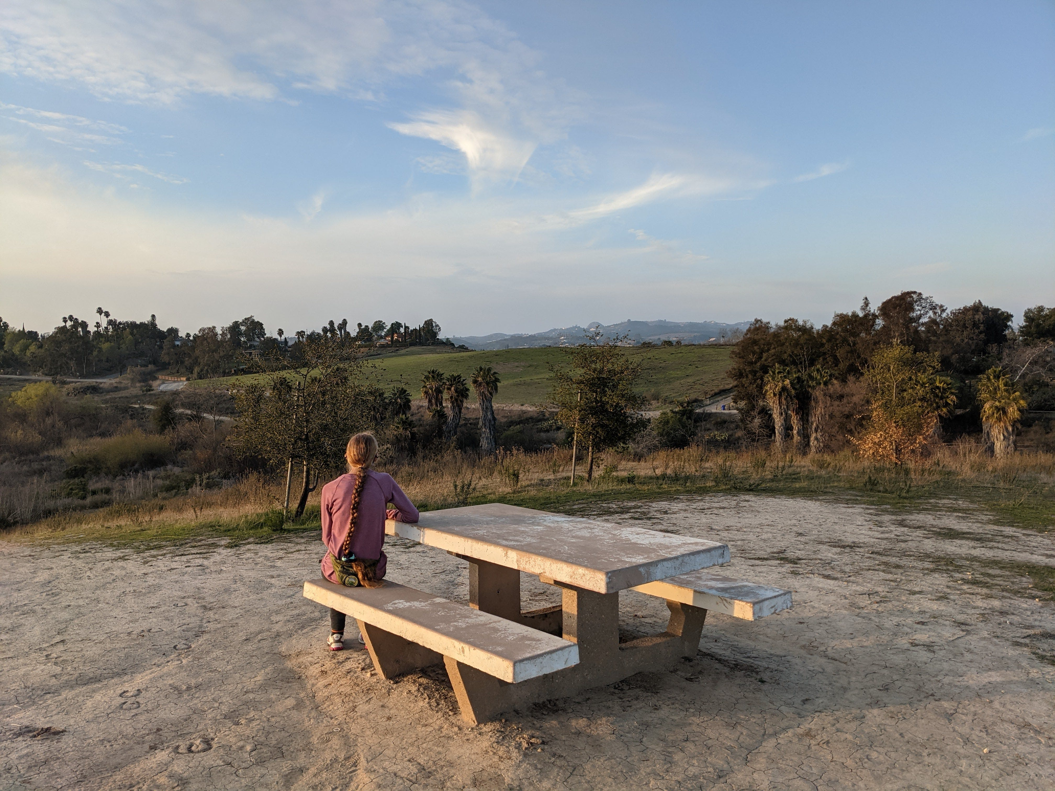 Woman sitting at a picnic table overlooking the trees and setting at Guajome County Park in San Diego