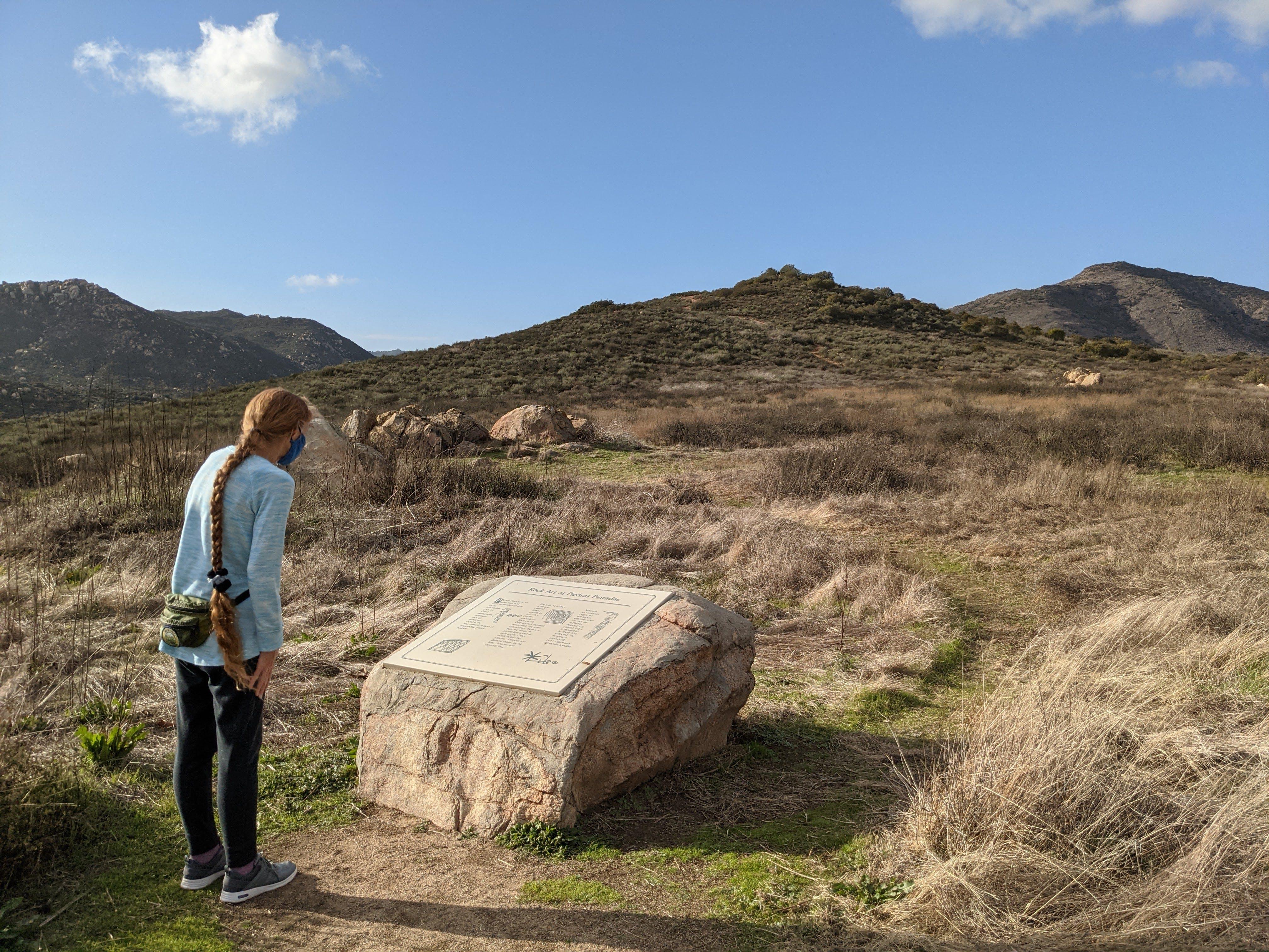 Woman looking at a placard rock sign at Lake Hodges Escondido San Diego County