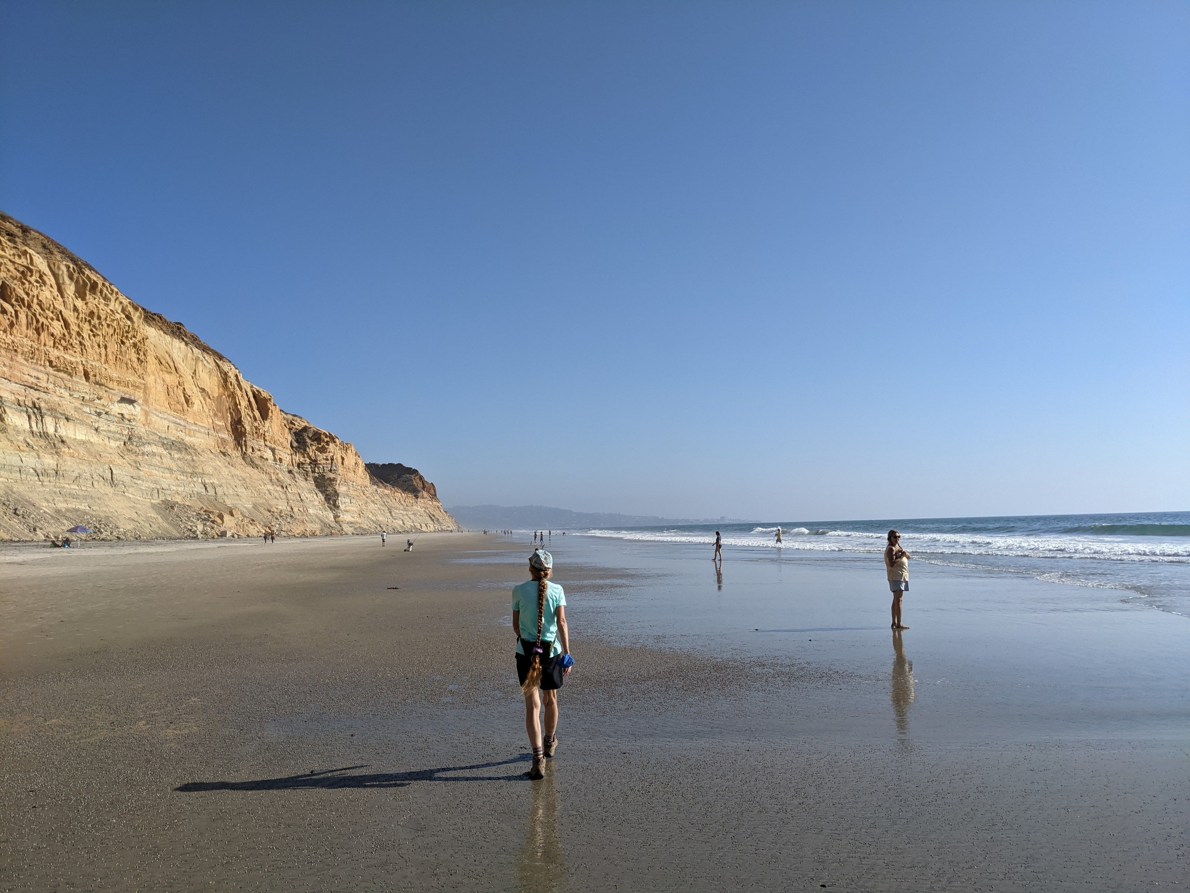 Hiker walking along the beach at Torrey Pines State Natural Reserve in San Diego County