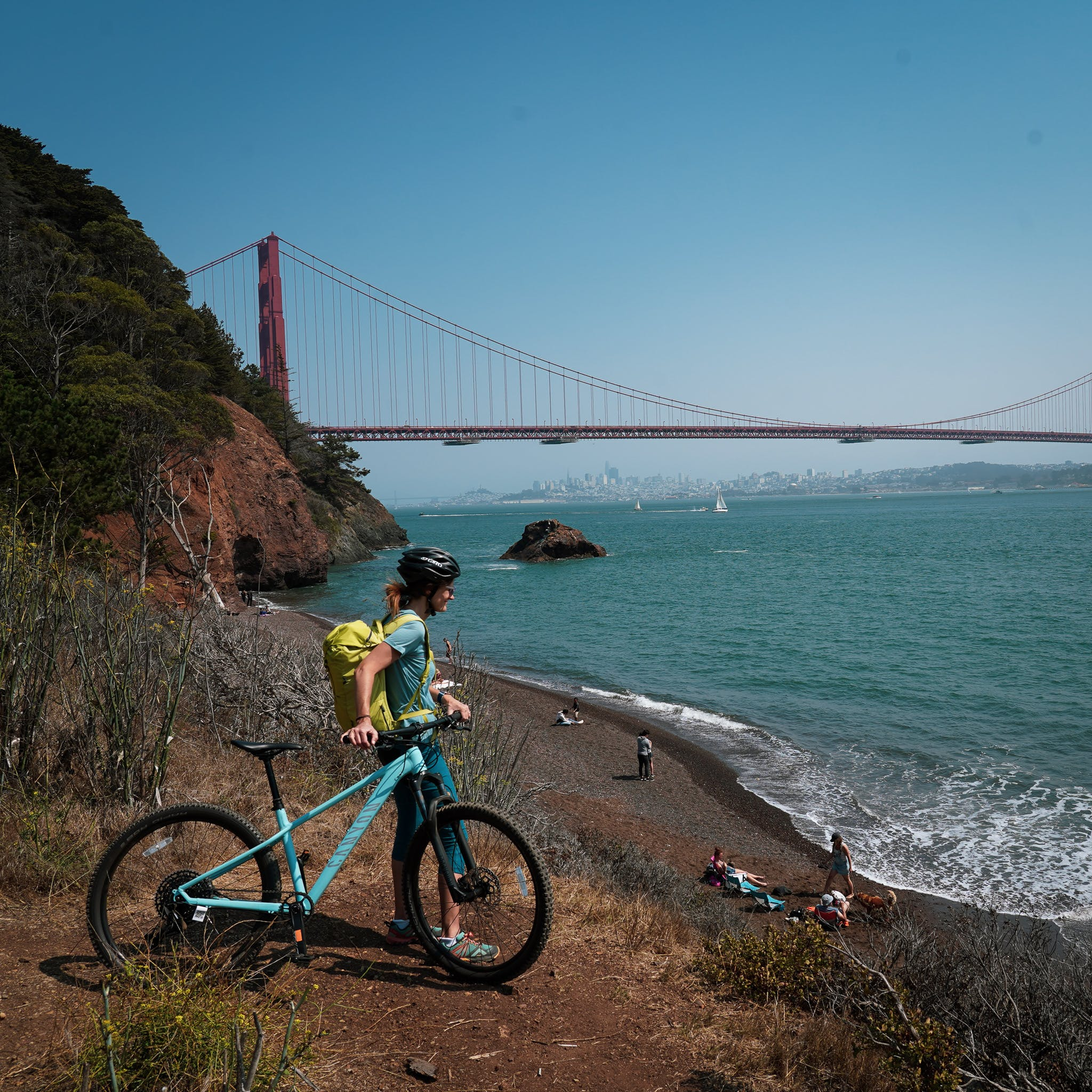 A biker with a yellow backpack standing at a vantage just above Kirby Cove Beach with the Golden Gate Bridge in the background