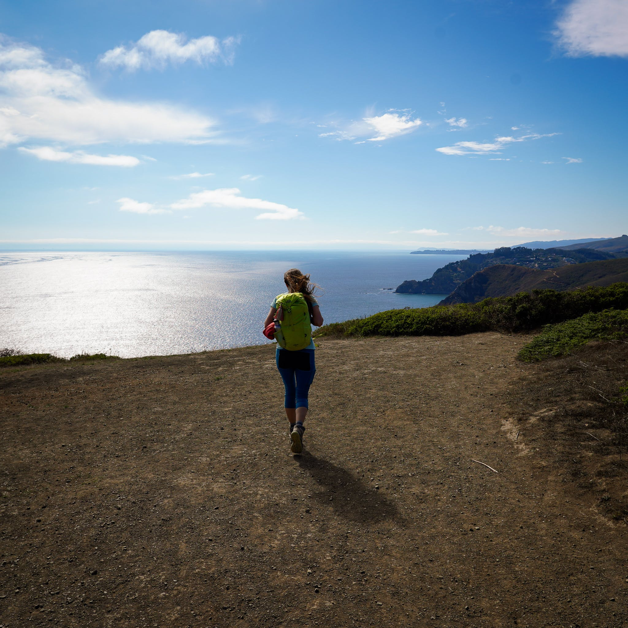 Woman standing at the top of Coyote Ridge and looking out to the Pacific ocean on the Coastal Trail in the Marin Headlands