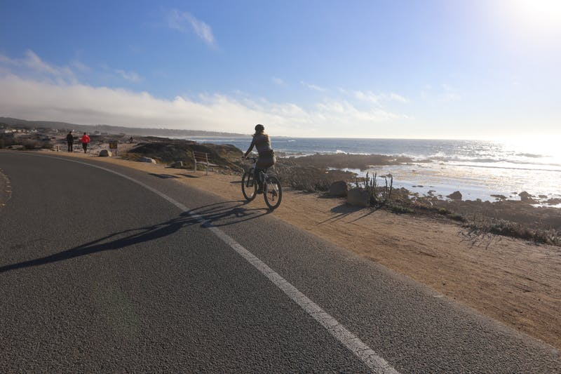 Woman on a bike riding alongside the coast and ocean in Monterey