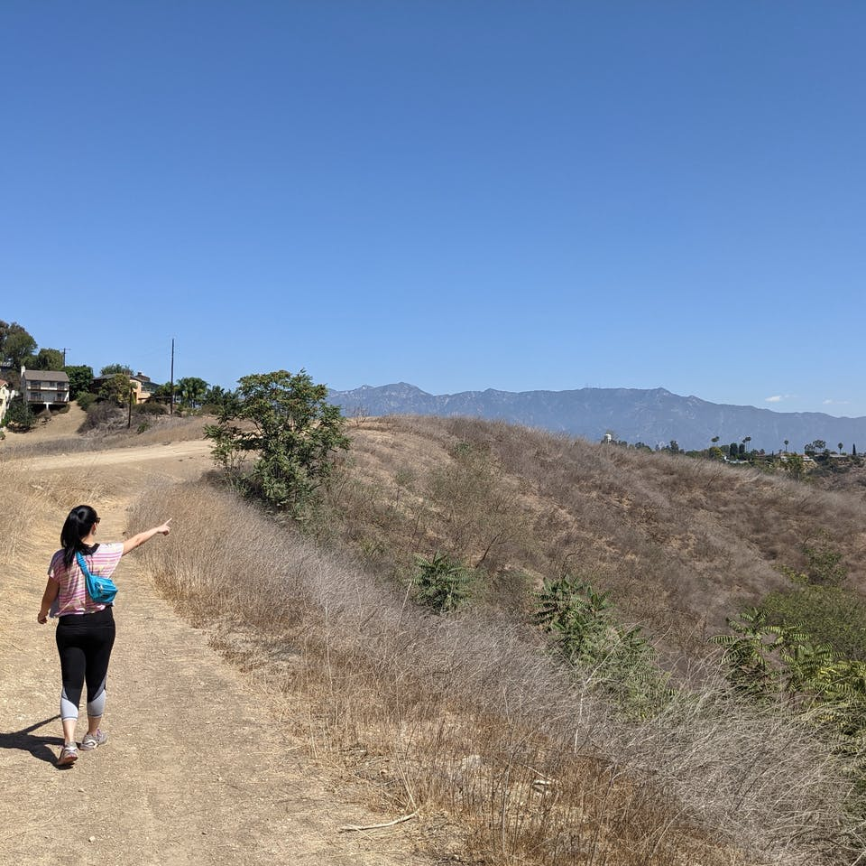 Hiker on trail pointing to surrounding hills at Elephant Hill Open Space in Los Angeles