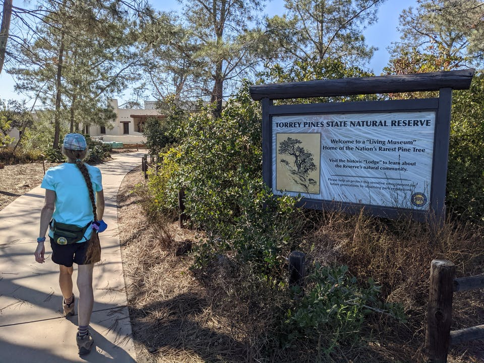 Hiker passing an information sign at Torrey Pines State Natural Reserve in San Diego County