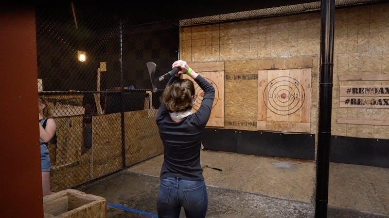 Woman throwing an axe at a target board at Reno Axe