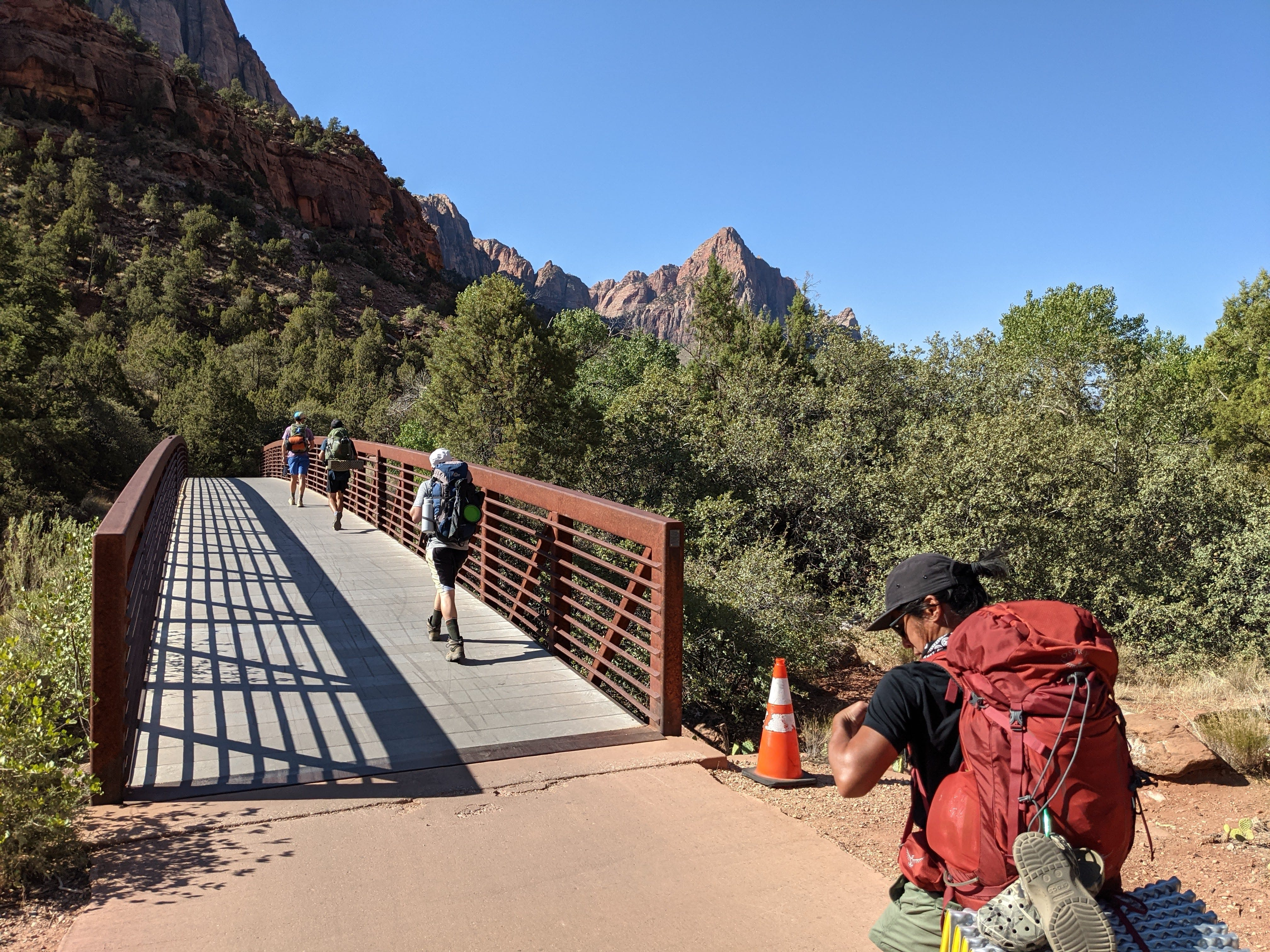 Hikers crossing a bridge on a backpacking trip in Zion National Park.