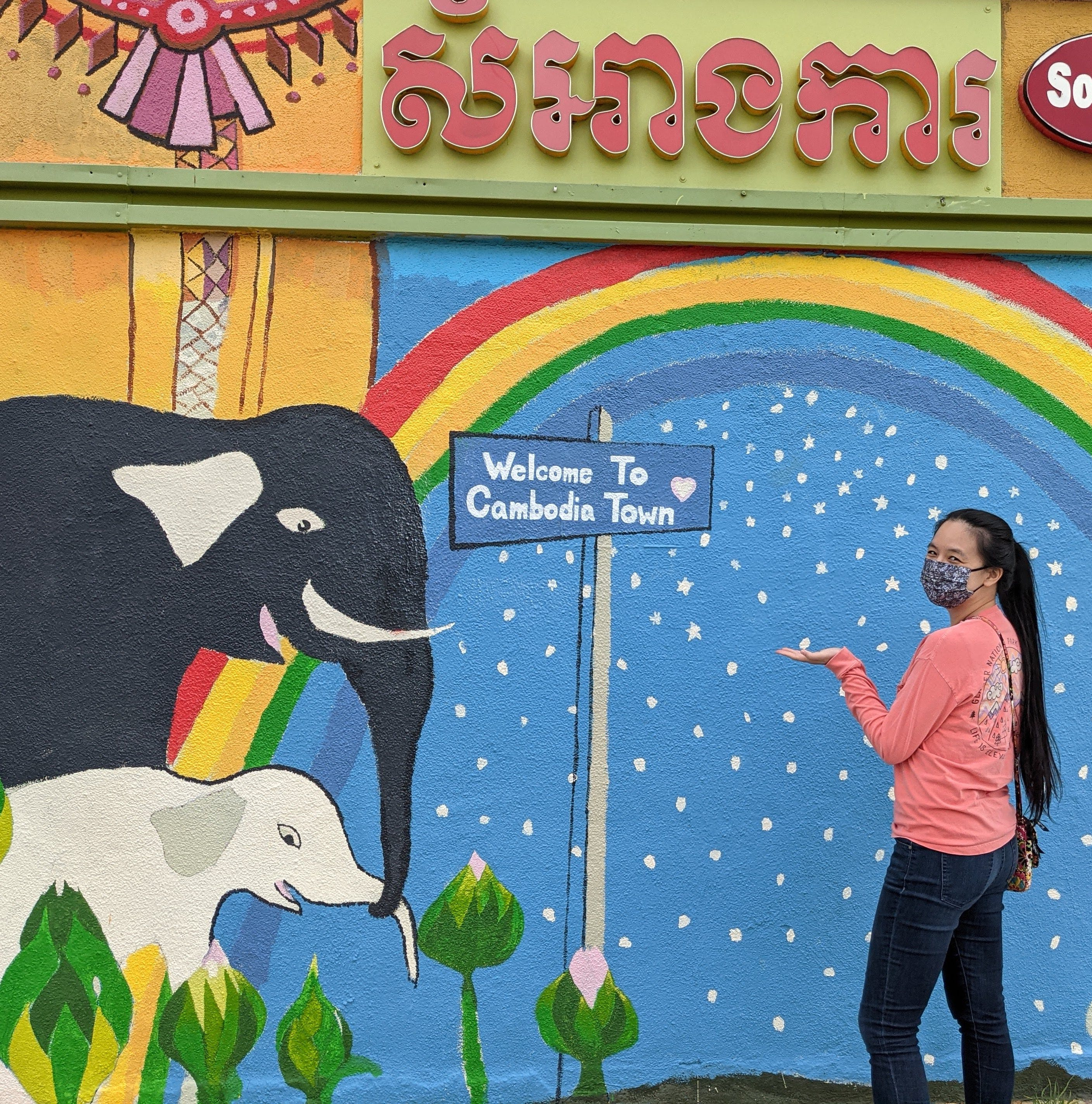 Woman standing at a mural welcoming here to Cambodia Town in Long Beach