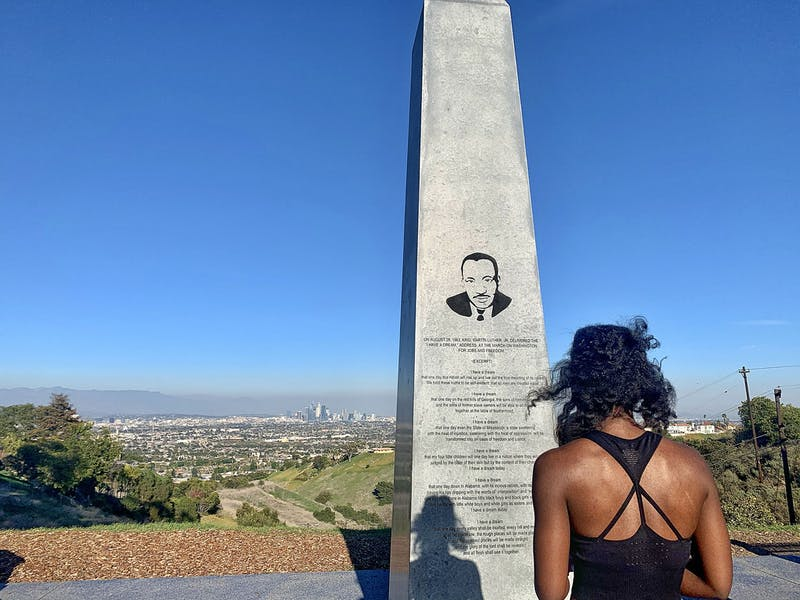 Woman standing at the Martin Luther King Jr. Memorial Tree Grove in Los Angeles