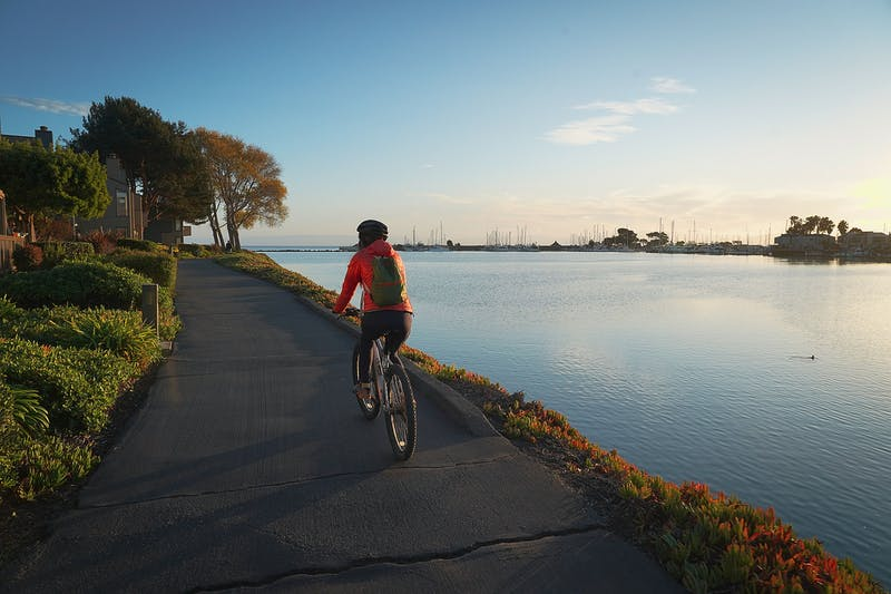 Woman biking waterside on car free trail in Alameda