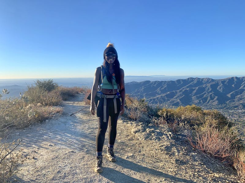 Woman smiling at the peak of Mount Lukens overlooking the San Gabriel Mountains