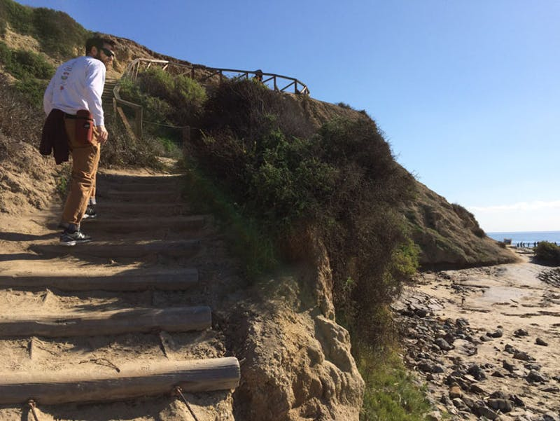 Person hiking up some stand stairs at Crystal Cove State Park.