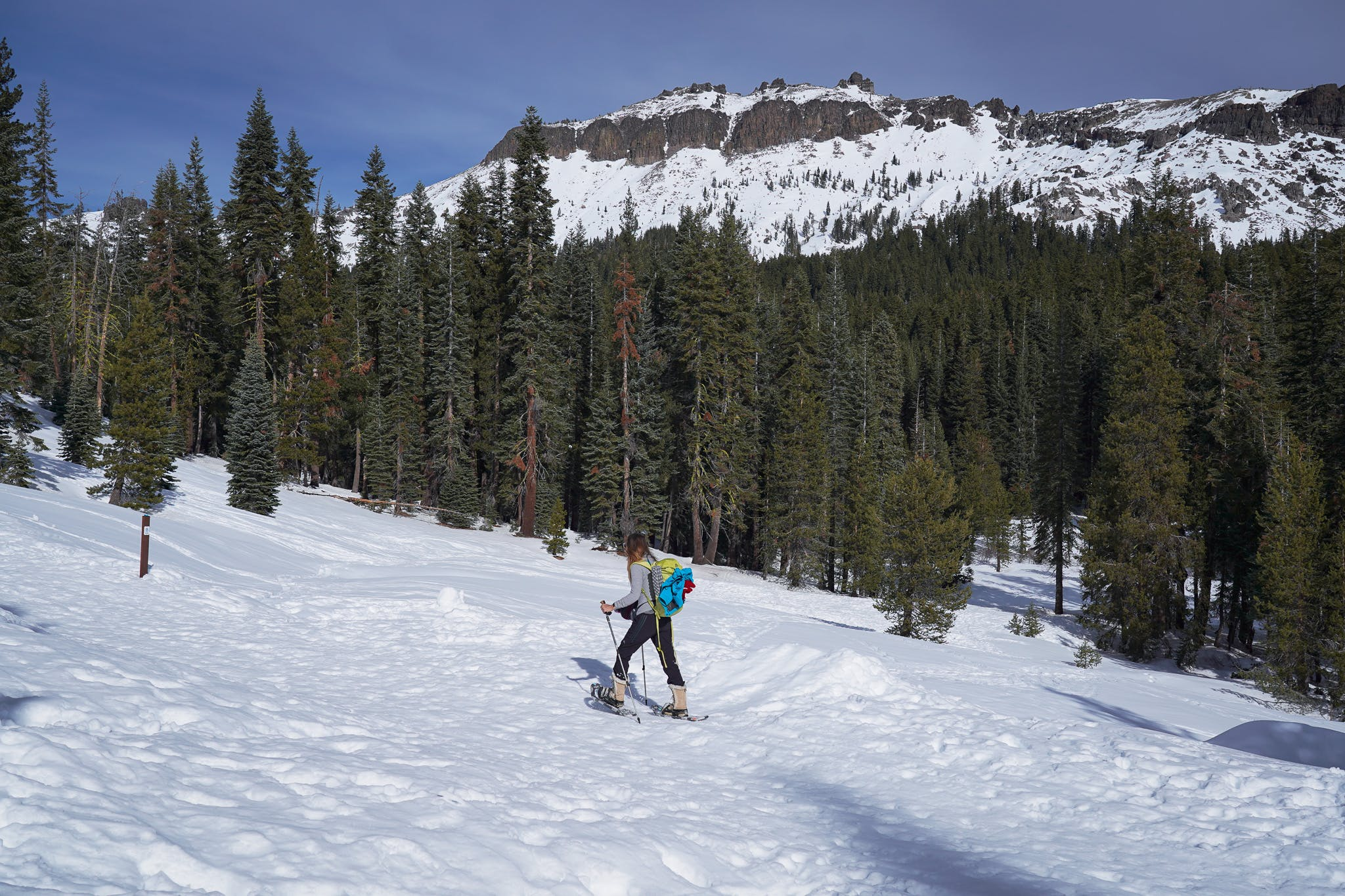 Woman snowshoe hiking up a trail to Castle Pass in Tahoe