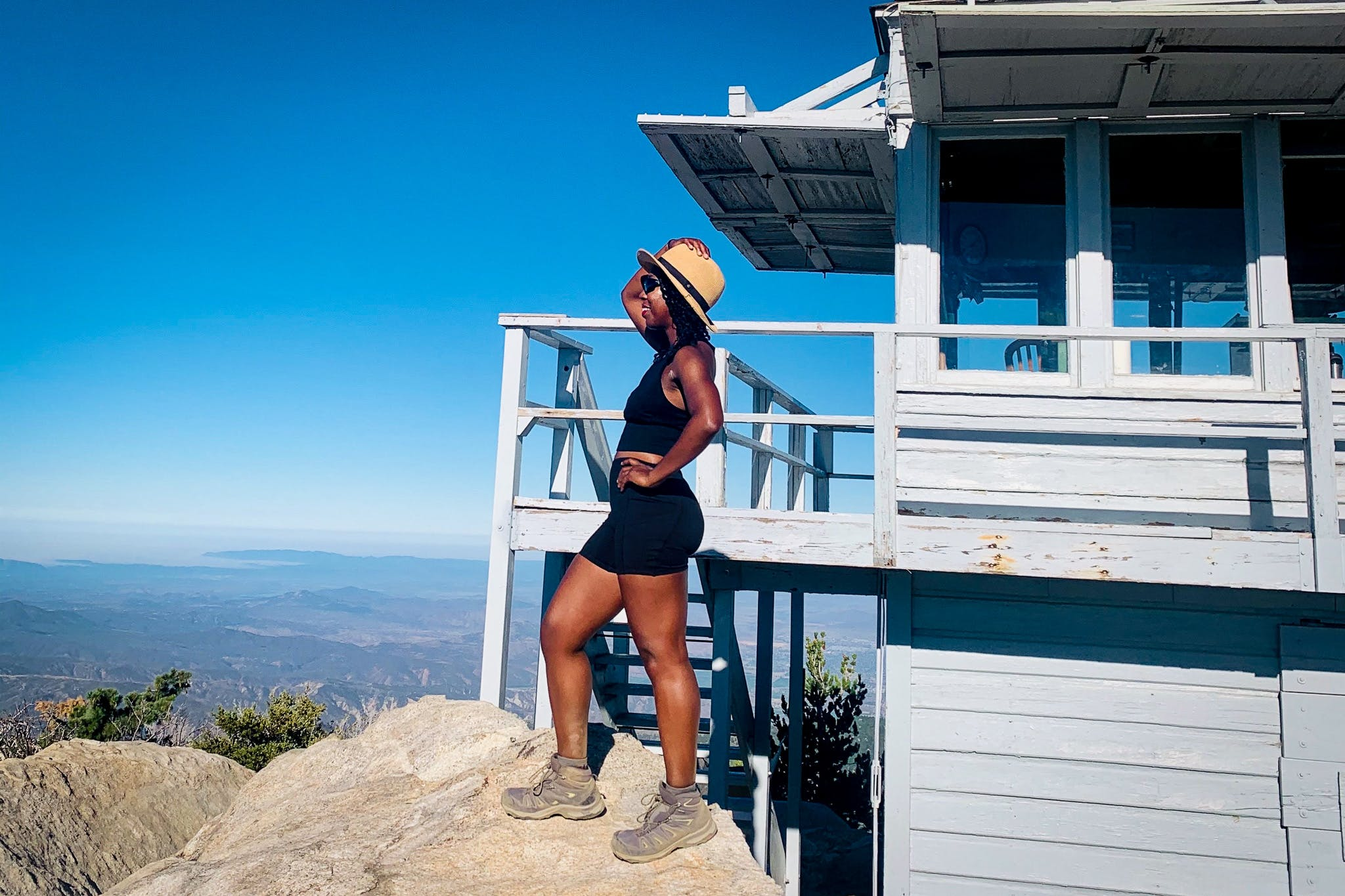 Woman standing at the lookout tower of Tahquitz Peak in the San Jacinto Wilderness in Southern California