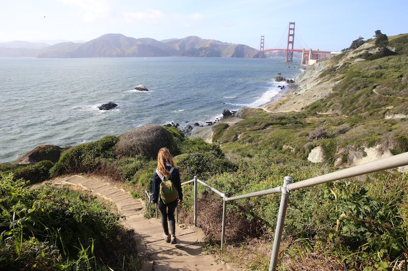 Woman walking down the stairs overlooking the ocean on the Coastal Trail in San Francisco