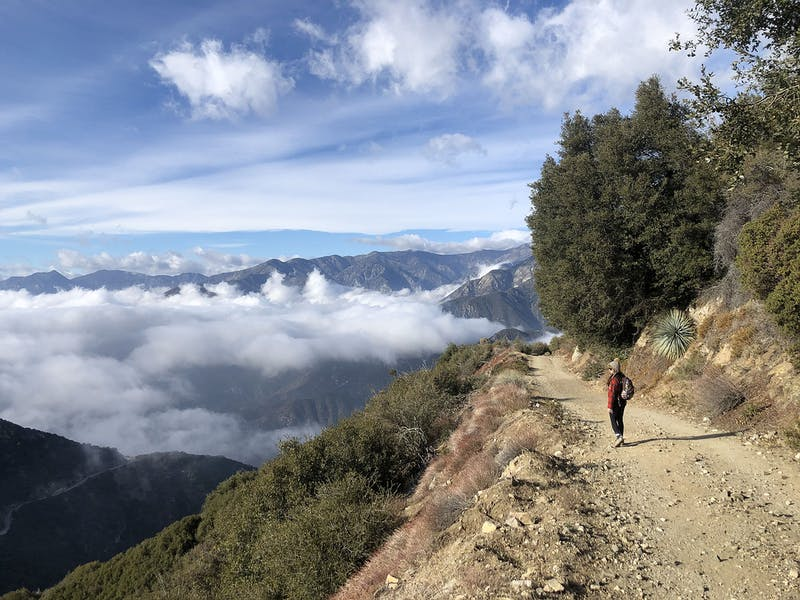 Woman hiking to Sunset Peak and looking at the San Gabriel Mountains blanketed by clouds